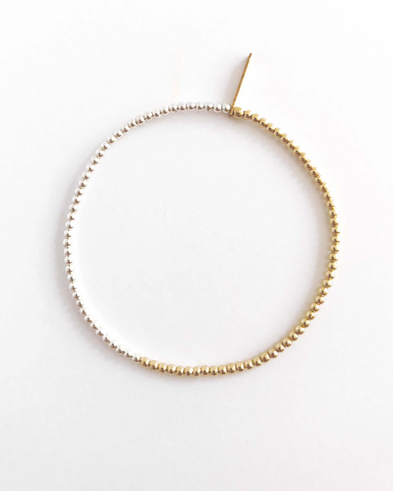 An understated modern bead necklace and bracelet jewelry collection designed by Nektar De Stagni. In this classic design, precious metals Gold and Silver are simply and elegantly paired.