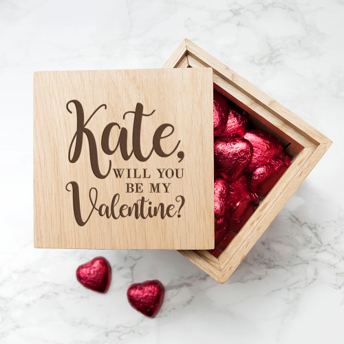 A wonderful way to ask them to be your Valentine!  The cube comes with a window on each side so you can display 4 photos of your choice. The lid is personalised with a name & can be lifted off to reveal 30 delicious Belgian chocolate hearts wrapped in a burgundy foil - one heart for every day of the month.  Once the month is over, you are able to use the cube as both a photo frame and a keepsake box. The perfect multifunctional, romantic gift.  Please note: may contain traces of soya or nuts.  The words 'Will you be my Valentine?' come as standard text