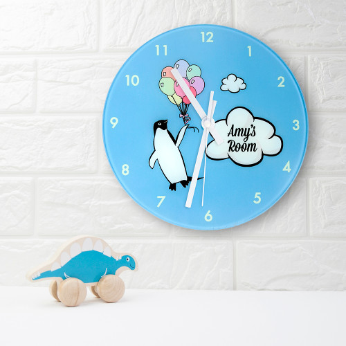 A fun and funky clock with adorable Percy the penguin!  Penguins can't fly, but we've given Percy the chance to experience it! With a bunch of bright and vibrant balloons Percy is flying as high as the clouds. Children will love how exciting and fun this clock is.  This 20cm glass wall clock is great to hang in their bedrooms.  Personalise with a name up to 15 characters.  The word 'Room' comes as standard text