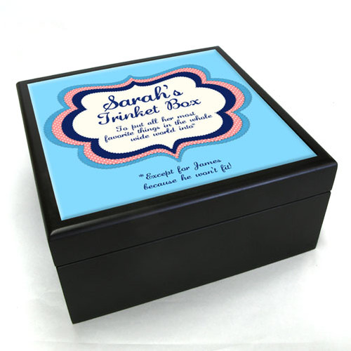 """Wooden jewellery box with personalised ceramic cover. Can be personalised with the recipient's name and something or someone they really love. Personalisation will read: """"Emily's Trinket Box, To put all her most favourite things in the whole wide world into ... Except for Sam and Jess because they won't fit!""""  Important Note: Name will appear exactly as entered including apostrophes. e.g. If the customer requires """"Elizabeth's Trinket Box"""" please enter """"Elizabeth's"""", rather than """"Elizabeth""""."""