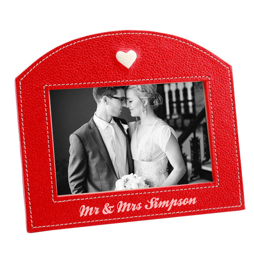 Bonded textured red leather photo frame, personalise with the happy couple's surnames. Heart design comes as standard Stitched boarder around the photo and the edge of the frame Finish this gift off with a picture of the couple Please fill in the personalisation fields to the right of the page.  Dimensions: 19cm x 14cm (Holds a 4x6 inch Photo)