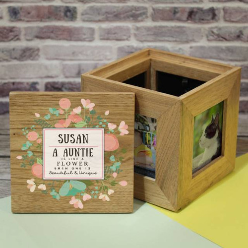 """Personalise this wooden photo cube with a name of up to 15 characters and their title (15 characters). The quote reads '{Name} A {Title} is like a flower each one is beautiful & unique'. The lovely sentiment is written in a white square surrounded by delicate flowers making this the perfect gift for any occasion. Please note as it is a natural wood product, colour and grain may slightly differ from box to box. The box is 11x11cm and holds four 3"""" x 3"""" photos."""
