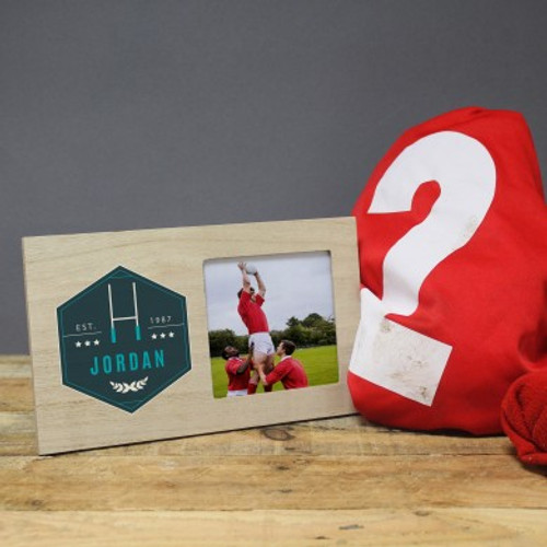 Personalise this rugby themed photo frame with a year and a name of up to 15 characters. Please note as it is a natural wood product, colour and grain may slightly differ from frame to frame. The frame is 15cm tall and 19cm wide with a strut back.