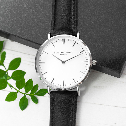 These beautiful modern-vintage watches by Elie Beaumont are carefully personalised by our craftsmen to create the ultimate gift for her.  Elie Beaumont watches are modern in design but with classic, timeless touches - making them a gift that will stand the test of time. Made from genuine leather and with a large 38mm dial with silver details this watch certainly makes a statement.  Personalise the watch on the reverse with a message up to 5 lines. The message is carefully engraved onto the back of the watch, meaning your special message will forever be remembered. (If you would like any or all of the lines left blank please use a / in each personalisation field)  The watch is beautifully presented in Elie Beaumont's trademark gift box and leather watch protector.  Movement: Miyota (Japanese) Water Resitant: 3ATM Case Width: 38mm Case Depth : 6mm Band Material: Stainless Steel Clasp Type: Fold-over Clasp Guarantee: 2 Years  Ladies watch.