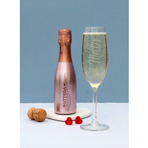 In this beautiful gift set there is a 200ml bottle of rose gold bottega prosecco and a personalised flute. Add a name using up to 15 characters, which will be engraved running along the side of the glass. The gift set is presented in a gift hamper making it the perfect finished gift to give to someone special. Glass Dimensions: H 21cm, W 6cm, D 6cm. Box Dimensions H 10cm, W 30cm, D 20cm. The glass is dishwasher safe.