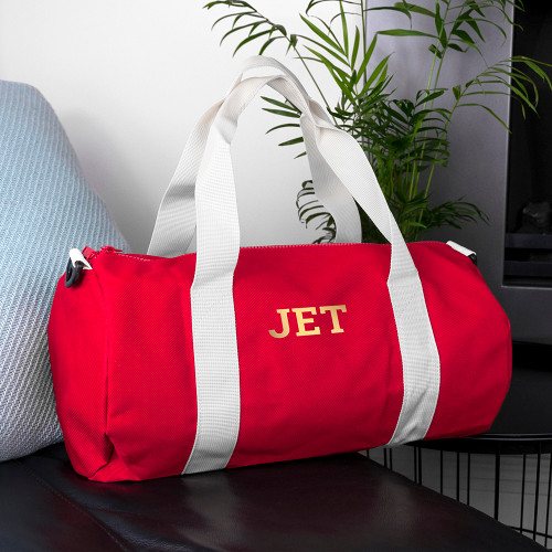 This stylish canvas barrel bag, doubling as gym bag and handy carry-on luggage, features a roomy main compartment to store all the essentials in. There's a small outside pocket that allows for easy access to a phone, wallet or keys.      It'll double as a hand-held bag or can be slung across the shoulder, with a shoulder strap that stretches from 70 cm to 120 cm, and is 4 cm wide.     The red and cream bag is monogrammable with up to three characters, making it a classically elegant and thoughtful gift.