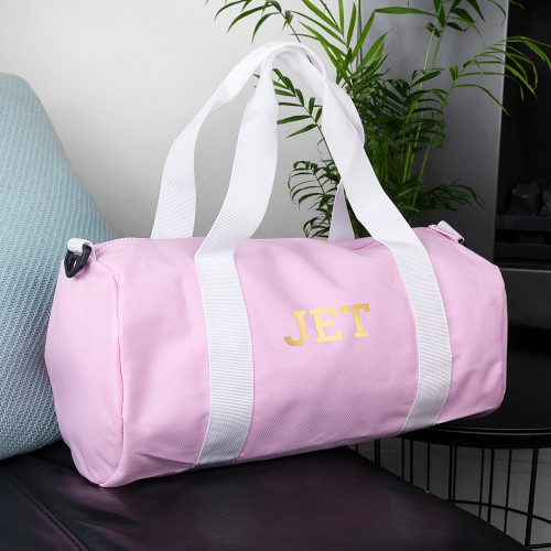 This stylish canvas barrel bag, doubling as gym bag and handy carry-on luggage, features a roomy main compartment to store all the essentials in. There's a small outside pocket that allows for easy access to a phone, wallet or keys.      It'll double as a hand-held bag or can be slung across the shoulder, with a shoulder strap that stretches from 70 cm to 120 cm, and is 4 cm wide.     The pink and cream bag is monogrammable with up to three characters, making it a classically elegant and thoughtful gift.
