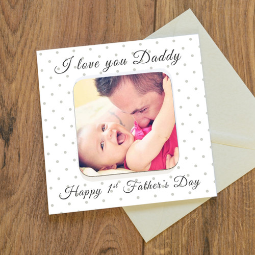 """A detachable drinks coaster forms the centrepiece of the card design. A card and a gift all in one! The card reads """" I or We love you Daddy"""" """"Happy 1st Father's Day"""", just add a photo to complete the design. Printed on quality 300gsm FSC certified board with a matching envelope. The inside of the card is left blank for your own personal message. Designed and made in the UK, the coaster is hardwearing with a glossy top. Individually cello wrapped for protection. Card 150mm x 150mm, Coaster 90mm x 90mm."""