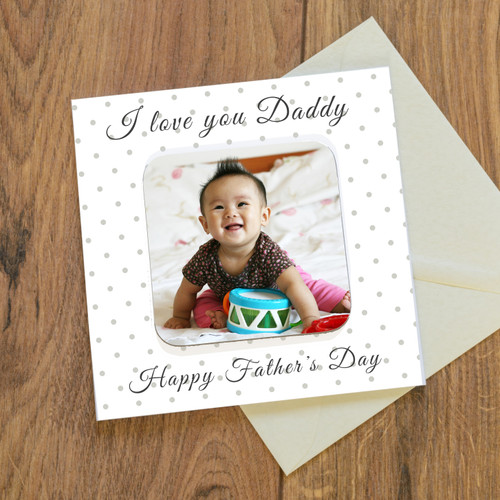 """A detachable drinks coaster forms the centrepiece of the card design. A card and a gift all in one! The card reads """" I or we love you Daddy"""" """"Happy Father's Day"""", just add a photo to complete the design. Printed on quality 300gsm FSC certified board with a matching envelope. The inside of the card is left blank for your own personal message. Designed and made in the UK, the coaster is hardwearing with a glossy top. Individually cello wrapped for protection. Card 150mm x 150mm, Coaster 90mm x 90mm."""
