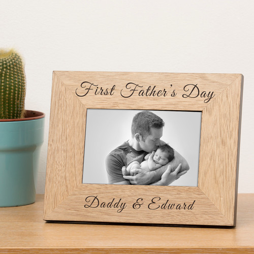 """A stylish personalised oak finish photoframe. The top is engraved """"First Father's Day"""". The bottom is engraved """"Daddy &"""" just add a name to complete the design. The frame holds a 6x4 photograph (outer dimensions are 220mm x 170mm)."""