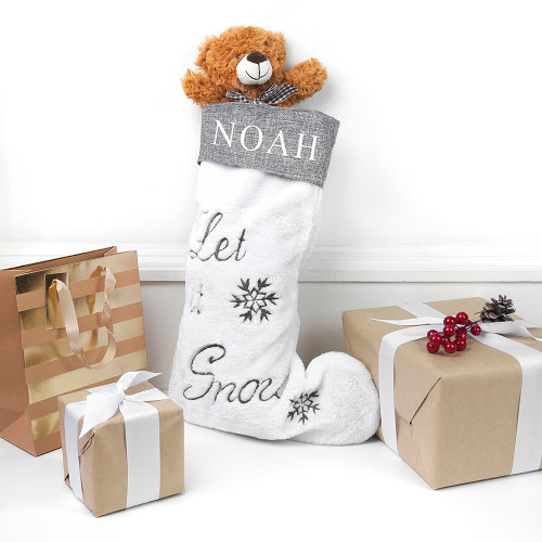 """Stockings are an amazing way to help sort and contain the little one's Christmas gifts on Christmas Day.  This stocking is white with grey trimming. It features two snowflakes in grey with a cursive """"Let it Snow"""" that comes as standard text.  The stocking can be personalised with a name, which will fo across the grey trimming on the top."""