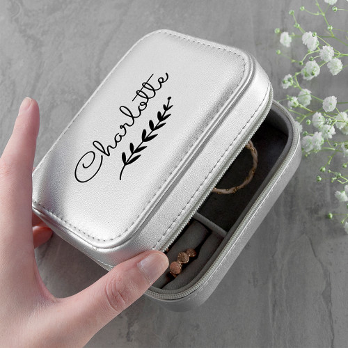 This silver leather case is perfect travelling kit in which to keep all your precious jewellery in. Securely closing with a zip and with a white suede-like interior, the interior boasts space for rings, necklaces and earrings, complete with a little mirror.  At 12 x 9 cm in size it's an ideal gift for jet setters and travellers, however if you know someone who treasures few key pieces of jewellery, it can sit as a keepsake on her night stand or vanity table.  The design features a wreath with a choice of name above the wreath.