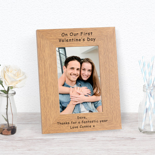 """A stylish personalised oak finish photoframe. The top of the frame is engraved """" On Our First Valentine's Day """", the bottom of the frame is left free for your own personalised message.The frame holds a 7x5 photograph (outer dimensions are 245mm x 195mm)."""