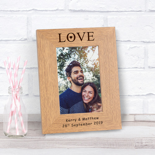 """A stylish personalised oak finish photoframe. The top of the frame is engraved """" Love"""", the bottom of the frame is left free for your own personalised message. The frame holds a 6 x 4 photograph (Outer dimensions are 220mm x 170mm) Available in both Portrait and Landscape."""