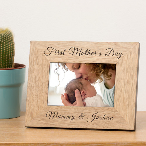 """A stylish personalised oak finish photoframe. The top is engraved """"First Mother's Day"""". The bottom is engraved """"Mummy &"""" just add a name to complete the design. The frame holds a 6x4 photograph (outer dimensions are 220mm x 170mm)."""
