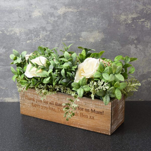 These artificial roses in a personalised wooden box are the perfect gift for any occasion! The wooden box can be personalised with a heartfelt message over 2 lines of 50 characters. It features artificial roses together with foliage. This artificial plant can be placed anywhere to give a natural look. The foliage is wipe clean only and the box measures 25cm tall, 42cm wide and 27cm depth.