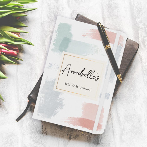 Add a name of up to 15 characters to this hardback notebook! The white soft feel A5 Notebook with matching elastic closure band and internal bookmark ribbon, contains approximately 80 lined pages. You can also add a message below your chosen name using 25 characters.