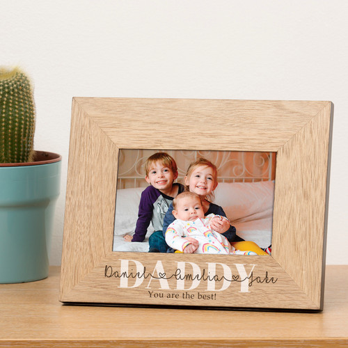 A stylish personalised oak finish photoframe. The recipient's name is printed in large capital letters (ie DADDY). Upto 5 additional names can be added in a script font running through the recipients name. A personalised message can be added to complete the design. The frame holds a 6 x 4 photograph (Outer dimensions are 220mm x 170mm)