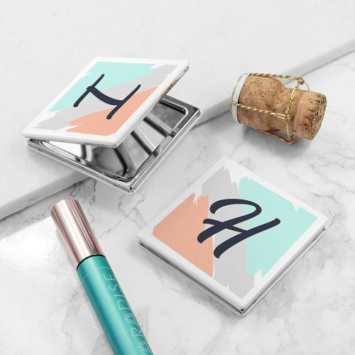 A square metal compact mirror which can be personalised with one initial.