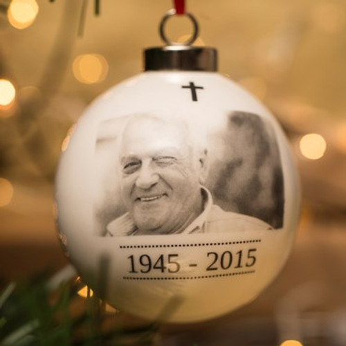 Whether you've recently lost a loved one or just want to commemorate their life, we know that it's nice to remember family members who are no longer with us.   Our personalised bauble makes a lovely, touching addition to the home and a great keepsake. Made from white bone china, you can choose a photo of your loved one to be printed below a cross motif and add a date span of your choice to appear inside a dotted lined border. You can also add a message to be printed on the back of the label in a black upper case font for that extra personal touch.   A thoughtful gift, whatever the occasion!   What Can I Put On My Bauble?   Personalise it with a photo, a date, using up to 11 characters and a message, using up to 60 characters to appear over three lines.   Use our innovative preview feature to see how it will look with your personalisation. Simply type in your chosen date and message, upload your photo and press the Preview button.  Dimensions: 6.6cm (diameter)  Material: Bone China