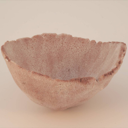 A thumb pot with a crusty white glaze over red earthenware clay.