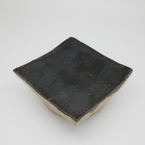 A small stoneware dish on a raised base with a black temmoku glaze. Use it for burning candles on, as a soap dish, a ring tray, cooking spoon rest, ...