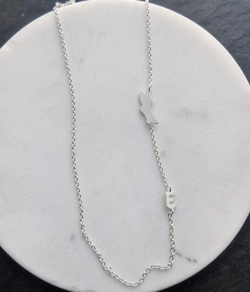 Sterling silver asymmetrical symbol necklace. Shown with Winged Foot and E.