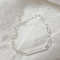 Engraved petite bar bracelet. Shown in sterling silver, cochin font. On elongated chain.