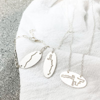 Running Map Jewelry. Shown left to right: Boston elongated bracelet, NYC on a cable chain, Chicago centered necklace.