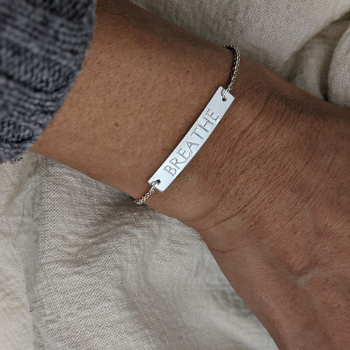 Engraved bar bracelet. Shown in sterling silver, roman font. Rolo chain.