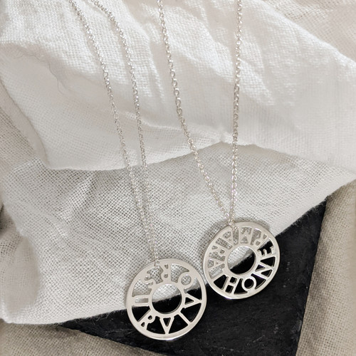 Handcrafted sterling silver mantra circle necklaces.