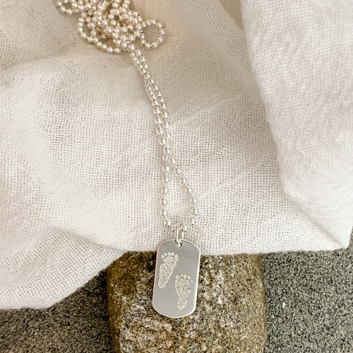 """Custom engraved baby footprints. Sterling silver shown on a 24"""" ball chain."""