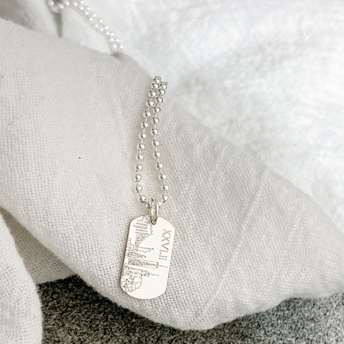"""Sterling silver dog tag engraved with the New York City skyline. Shown on a 24"""" ballchain"""