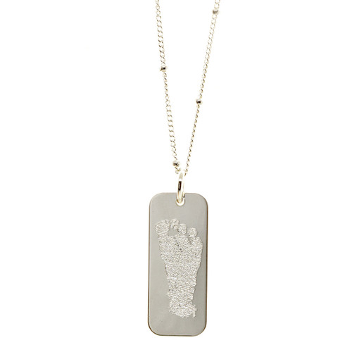 Custom engraved baby footprint necklace. Shown in sterling silver on satellite chain.
