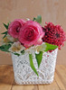 The 4 inch square stiffened lace vase cover has a scalloped edge and is 4.5 inches tall. Can be used as a basket or to cover vases.