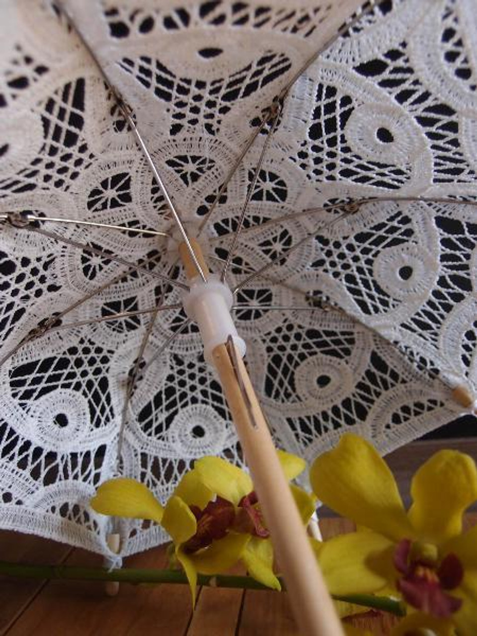 Decorative parasol that features an intricate cutwork and battenburg lace design. Each lace parasol has a bamboo handle & ferrule and stainless steel ribs.