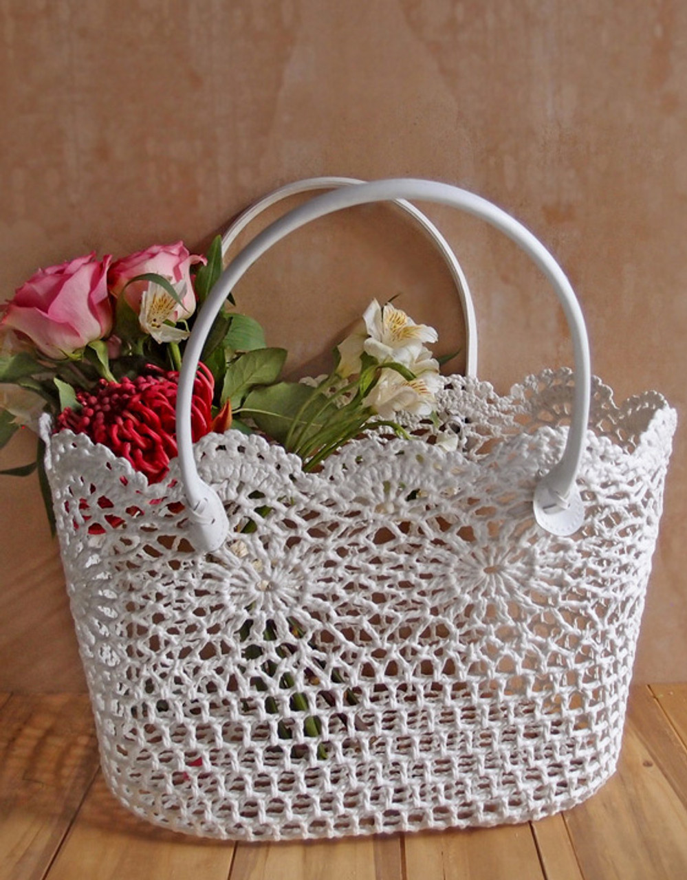 "This stylish lace flower basket measures 15""L x 10.25""W x 9.5""H. It has padded vinyl covered handles. Made with stiffened lace."