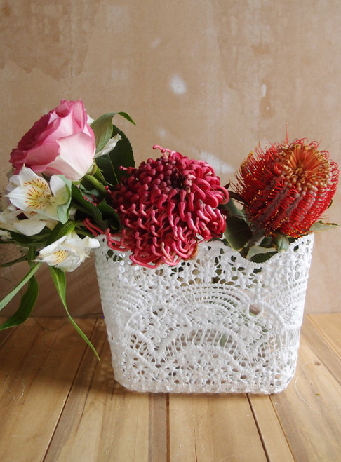 The 6 inch square stiffened lace vase cover has a scalloped edge and is 6.5 inches tall. Can be used as a basket or to cover vases.