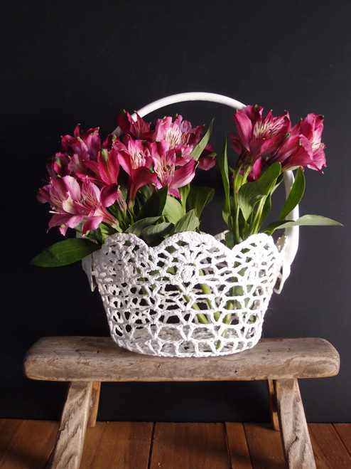 This stiffened lace basket has a cushioned handle. The basket is 4 inches x 5 inches.