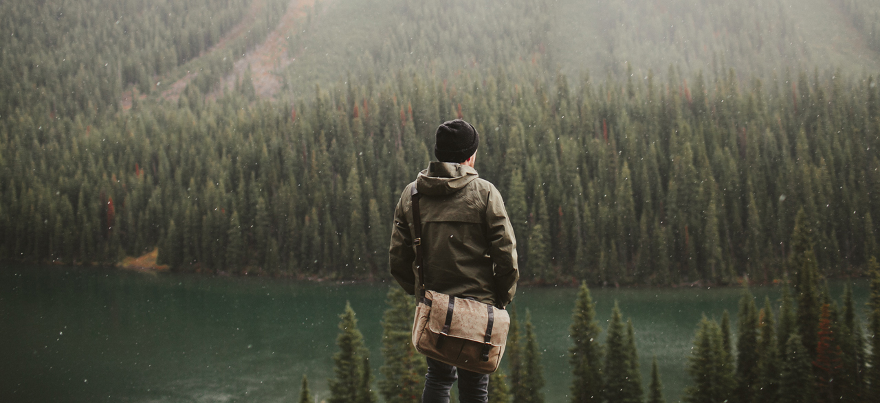 Man staring at lake and forest