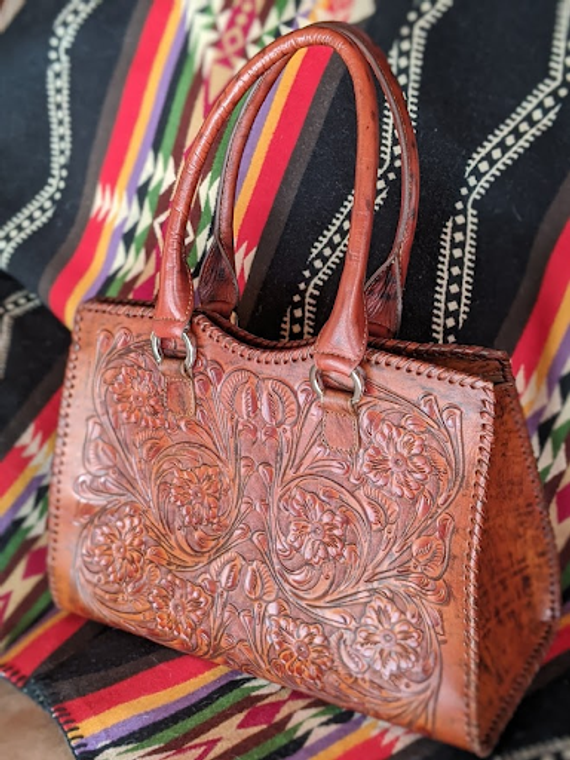 This beautiful leather bag features stunning hand tooled designs, hand lacing and quality craftsmanship. A zippered enclosure will keep your valuables safe while a luxurious set of 4 internal pockets - 2 zippered, 2 open - will keep them organized. The interior soft leather lining provides additional, enduring protection.