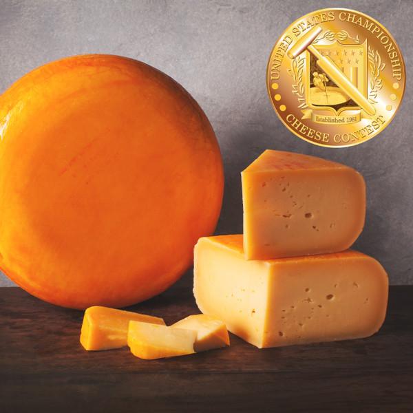 orange wheel of cheese and wedges of orange cheese on wood board