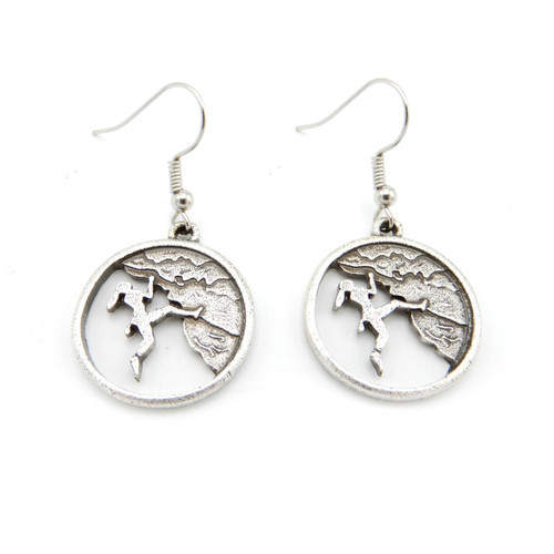 Direct view of a pair of silver earrings featuring a cutout of woman mountain climbing. Active Jewelry for your active lifestyle