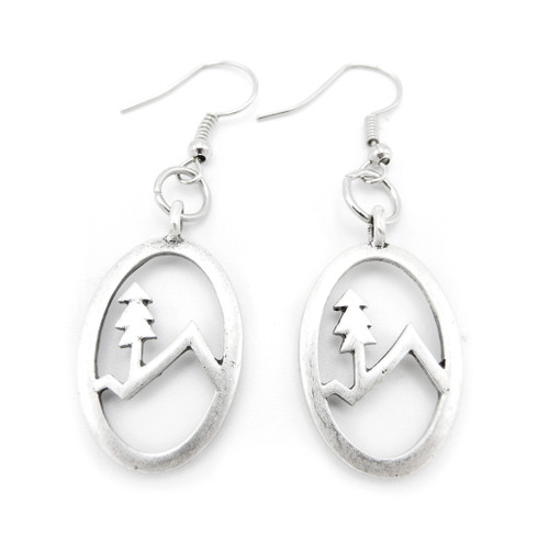 A silver pair of earrings from LILO Collections featuring a silhouette of a tree and mountain