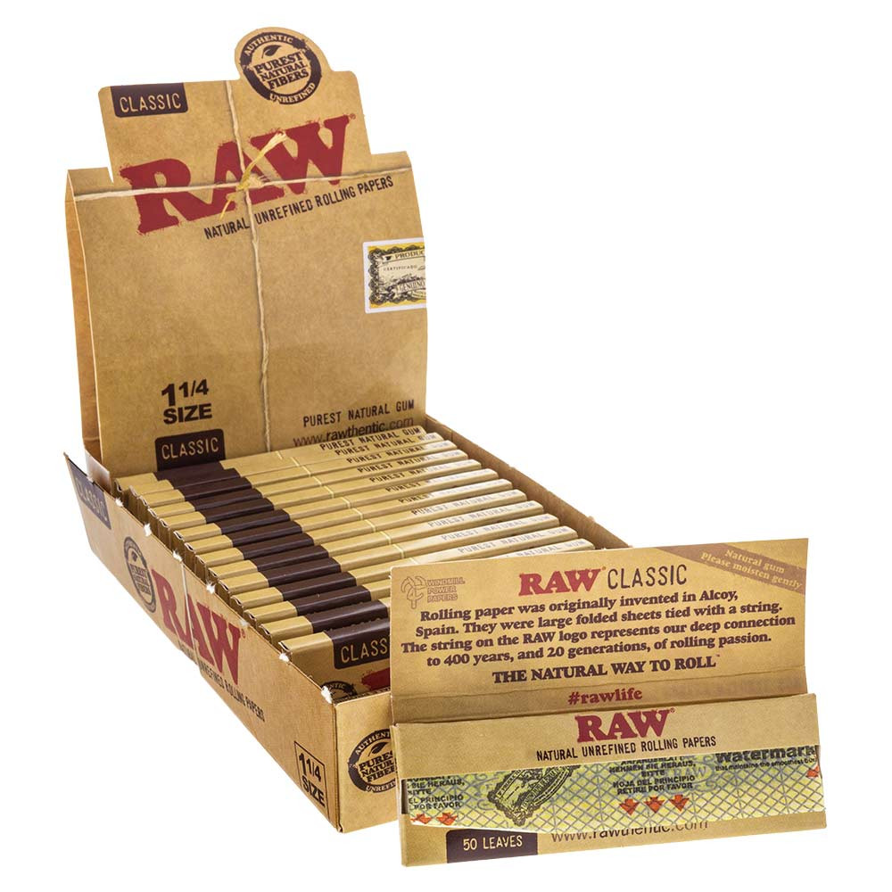 An open display box of Raw Classic 1 1/4 Rolling Papers filled with booklets with a single one next to it.