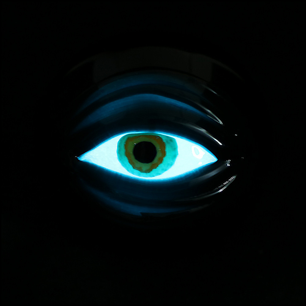 The front eyeball glowing in the dark under a blacklight.