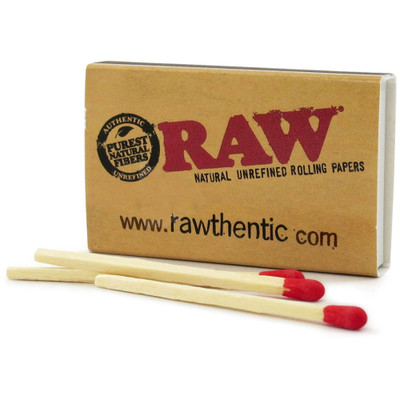 Closed box of Raw Wooden Matches with a few matches loosely placed in front.