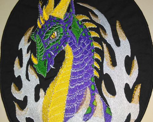 "Purple, yellow, and green dragon head with flames  9"" x 11""  Black border"