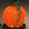 Glass pumpkin, Orange classic style pumpkin, all glass, handsculpted in Sherwin Art Glass studio in Bellows Falls, Vermont by glass artisan Chris Sherwin. Showcased here glowing glass pumpkin on black round illuminating light base.