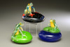 Frog grouping, featuring Costa Rica Frog on deep cobalt Starry Nights pedestal, Green Frog on lily pad, and Green Frog on lily pad over water, hand-made & solid sculpted glass.